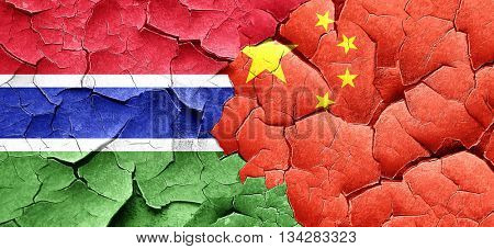 Gambia flag with China flag on a grunge cracked wall