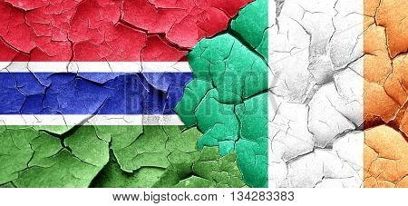 Gambia flag with Ireland flag on a grunge cracked wall
