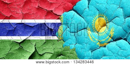 Gambia flag with Kazakhstan flag on a grunge cracked wall