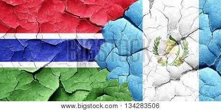 Gambia flag with Guatemala flag on a grunge cracked wall