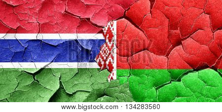 Gambia flag with Belarus flag on a grunge cracked wall