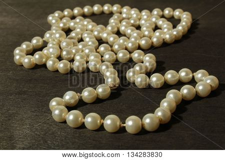 White Pearls Necklace On Black Wood Background