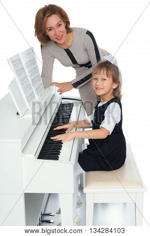 Diligent little girl plays the piano under the guidance of a teacher - Isolated on white background
