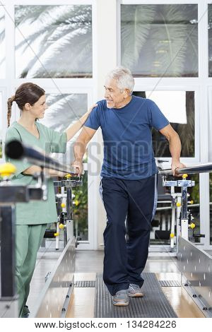 Patient Looking At Young Physiotherapist While Walking In Fitnes