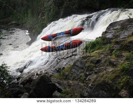 Men transfer inflatable catamaran on land because dangerous waterfall