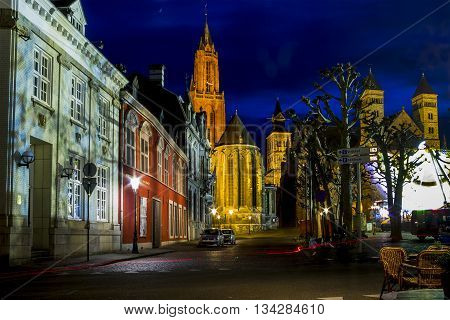 MAASTRICHT, NETHERLANDS - MAY 15, 2013: It is a night view of the illuminated red bell tower of St. Nicholas Church.