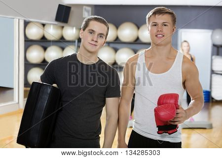 Friends Holding Boxing Gloves And Bag In Gym