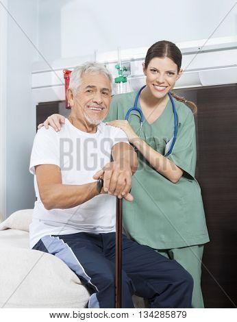 Nurse With Arm Around Patient In Rehab Center
