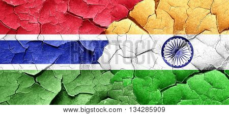 Gambia flag with India flag on a grunge cracked wall