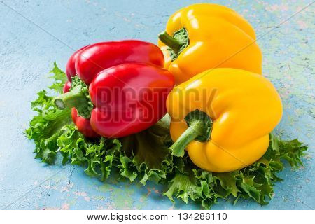Fresh organic red and yellow bell peppers and lettuce on old blue table. Selective focus