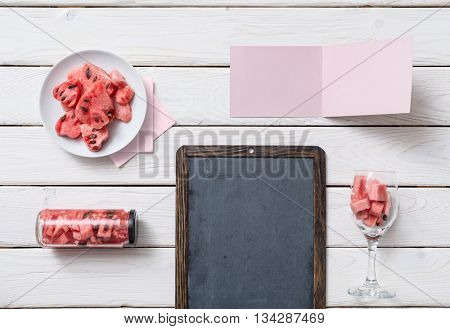 Mockup of chalkboard and greeting tag on white desk with sliced watermelon. Top view.