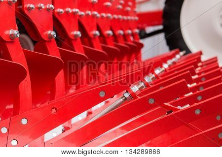 Rows of red enameled elements of agricultural machine part of combine harvester