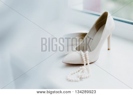 Ivory female wedding footwear with pearls juweliry on the window.