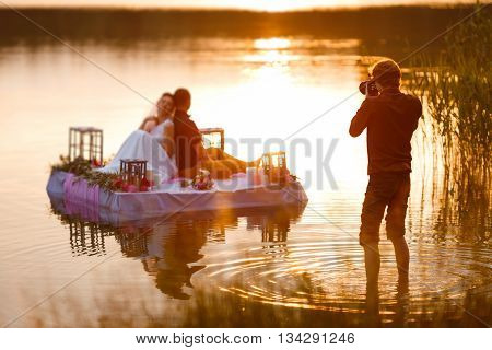 Wedding photographer in action taking a picture of the bride and groom sitting on the raft. Summer sunset.
