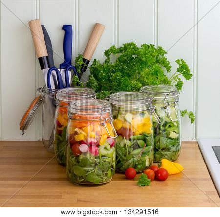 Prepared salad in glass storage jars with kitchen utensils and parsley.