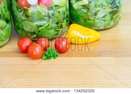 Prepared salad in glass storage jars with tomatoes and sweet pepper. Copy space.