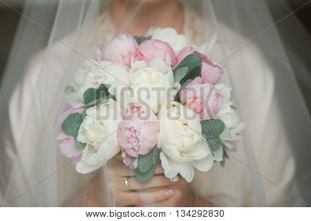 Charming and delicate bride holding bouquet with peonies and eucalyptus. Pink and white peonies under the veil of the bride