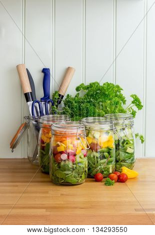 Prepared salad in glass storage jars in kitchen with utensils. Space for text. Vertical.