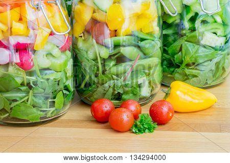 Prepared salad in glass storage jars. Close up.