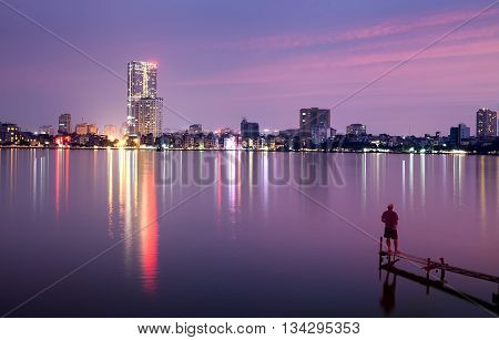 HA NOI, VIET NAM, May 14, 2016 the scenery of West Lake, Ha Noi center, at night, shimmering electric light. The man is fishing