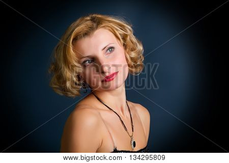 Portrait of beautiful blonde girl on dark background with copyspace