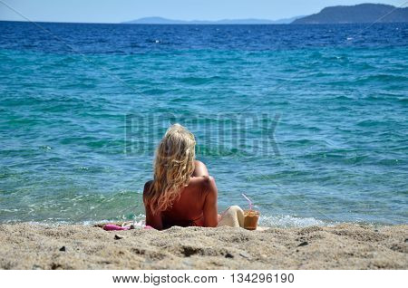 Blond woman relaxing on beach enjoying cold coffee frappe and looking at open sea