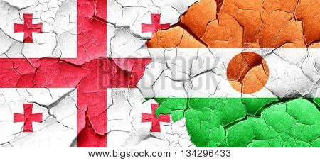 Georgia flag with Niger flag on a grunge cracked wall