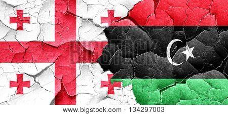 Georgia flag with Libya flag on a grunge cracked wall