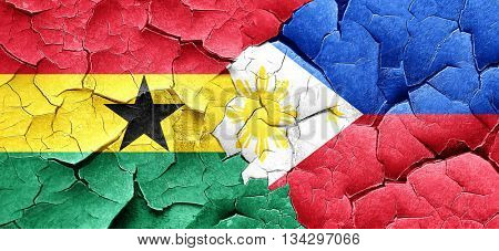 Ghana flag with Philippines flag on a grunge cracked wall