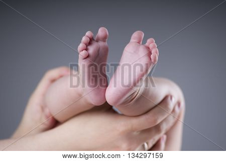 Baby foot in mother's hands on gray background