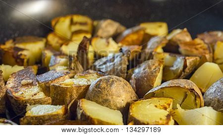 Alot of roasted potato in a frying pan on wooden table