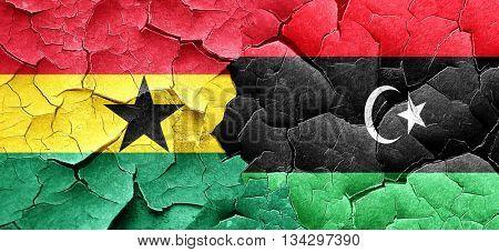 Ghana flag with Libya flag on a grunge cracked wall