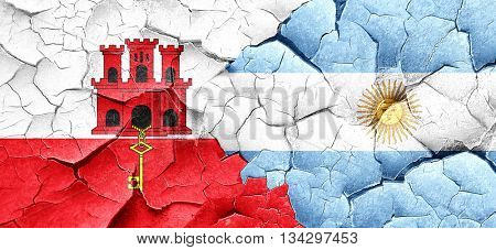 gibraltar flag with Argentine flag on a grunge cracked wall