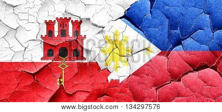 gibraltar flag with Philippines flag on a grunge cracked wall