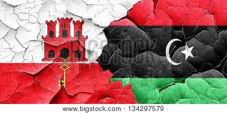 gibraltar flag with Libya flag on a grunge cracked wall