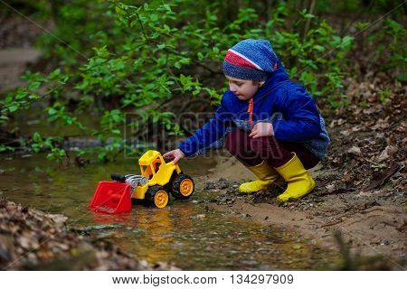 photo of little funny boy playing with excavator