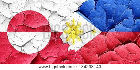 greenland flag with Philippines flag on a grunge cracked wall