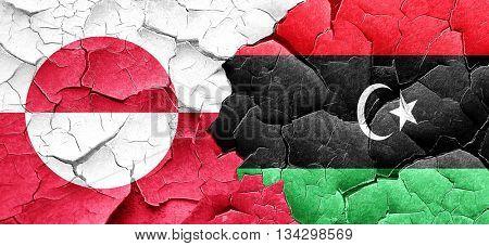 greenland flag with Libya flag on a grunge cracked wall