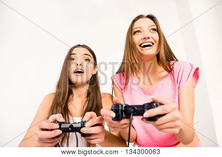 Cheerful joyful girlfriends playing video games with joysticks on the bed