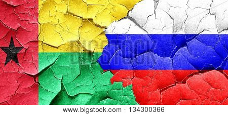 Guinea bissau flag with Russia flag on a grunge cracked wall
