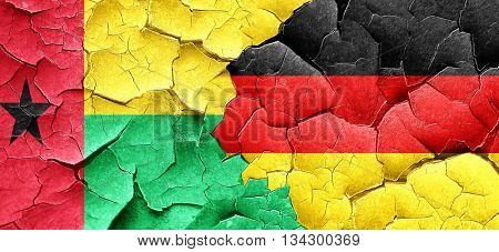 Guinea bissau flag with Germany flag on a grunge cracked wall