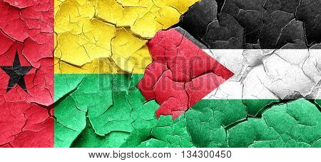 Guinea bissau flag with Palestine flag on a grunge cracked wall