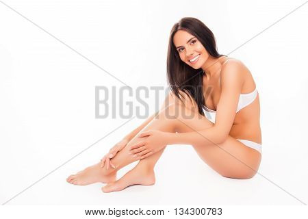 Pretty Woman In White Underwear Doing Massage For Her Legs