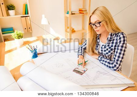 Portrait Of Young Engineer Using Calculator To End The Project