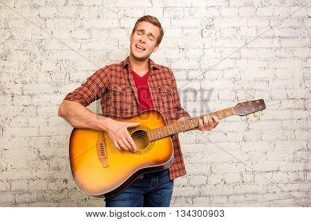 Handsome young man in red shirt playing on the guitar and singing