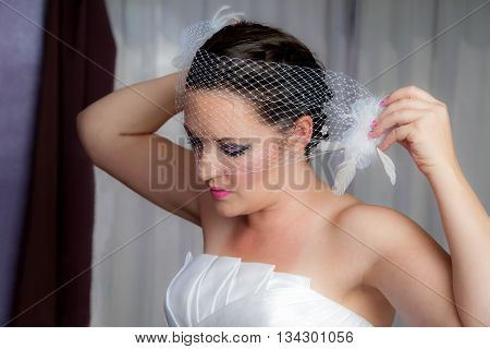 A bride getting ready for her wedding. She is putting on her birdcage veil.