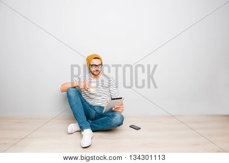 Handsome Hipster Man In Hat And Spectacles Sitting With Tablet And Coffee