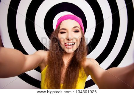 Comic Girl In Pink Hat Winking And Showing Tongue While Making Selfie