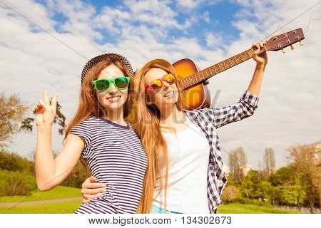 Portrait Of Beautiful Women In Glasses Holding Guitar In The Park