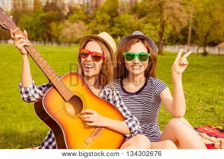 Cheerful Happy Girls Having Picnic And Playing On Guitar